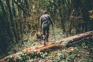 Man Traveler hiking in wild boxwood
