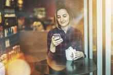 Smiling hipster girl using cellphone