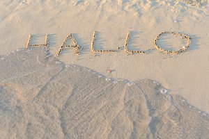 Written words Hallo on sand of beach