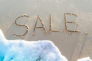 Word Sale handwritten in sand