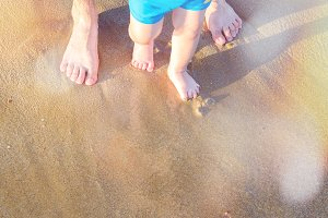 Baby doing his first steps on the beach