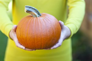 Woman holding orange pumpkin