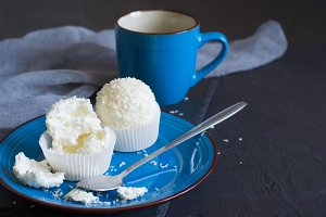 Small meringue cakes Pavlova with glaze and coconut On a blue pl