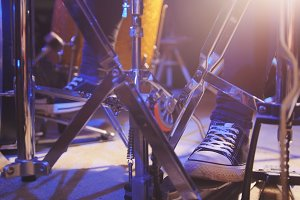Drummer's foot wears sneakers moving drum bass pedal