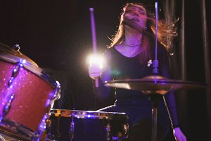 Teen rock music - girl with flowing hair percussion drummer performing with drums