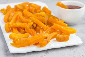Healthy baked sweet potato fries on white plate served with spicy sauce
