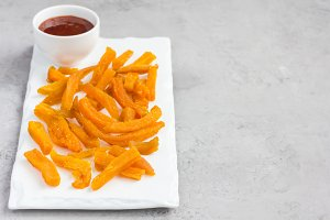 Healthy baked sweet potato fries on white plate served with spicy sauce, copy space
