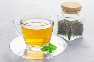 Herbal mint tea in a glass cup with fresh peppermint on background, horizontal
