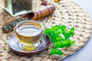 Healthy herbal mint tea in oriental glass cup with fresh peppermint and tea scoop on background, horizontal, copy space
