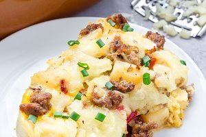Egg casserole with potatoes, sausage and pepper, on white plate, vertical