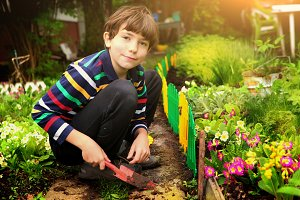 preteen handsome boy work in the garden