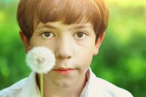 preteen handsome boy blow with dandelion
