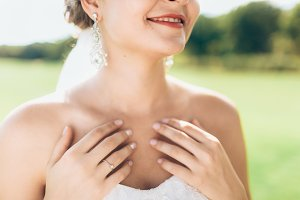 The bride in a white dress holding hands near her neck