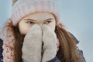 teen girl close up portrait in knitted hat and mittens