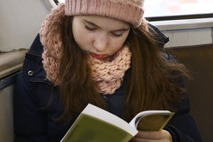 girl in knitted hat and mittens read in train