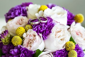 Wedding rings on bouquet of pink and purple flowers