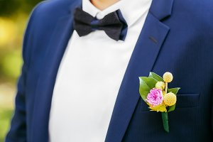 Pink peon boutonniere pinned to a grooms jacket