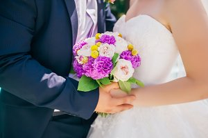 Newlyweds holding delicate marriage bouquet