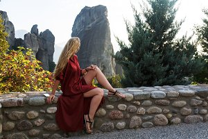 Beautifulr woman in flying red dress sitting on the rock wall over valley background