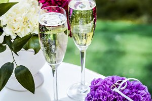 Small table with glasses with champagne and wedding rings