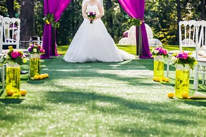 Bride standing in wedding archway with chairs on on each side