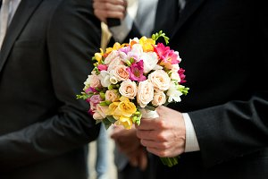 Man holds wedding bouquet