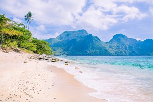 Stunning beach on Helicopter Island in the Bacuit archipelago in El Nido, Cadlao Island in Background, Palawan, Philippines