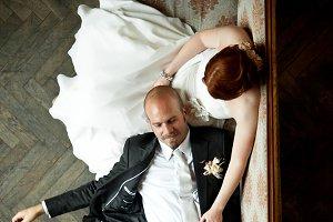 Stylish groom lies on bride's knees