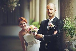 Funny bride hides behind a groom