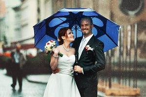 Happy couple under the blue umbrella