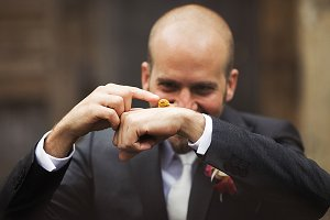 Stylish groom plays with a snail