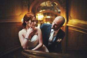 Bald-headed groom looks at a bride