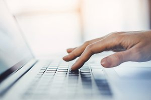 Hands typing on the laptop keyboard