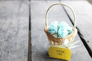 Spring sale tag and flowers in a small basket. Vintage Retro Or Rustic Style