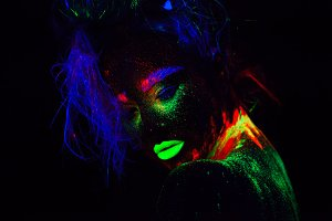 Beautiful extraterrestrial model woman with blue hair and green lips in neon light. It is close portrait of beautiful model with fluorescent make-up, Art design of female posing in UV with colorful make up. Isolated on black background