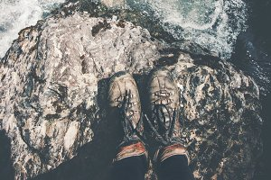 Feet trekking boots on stone