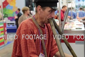 A folk musician plays simultaneously on two pipes, a cap, a smile