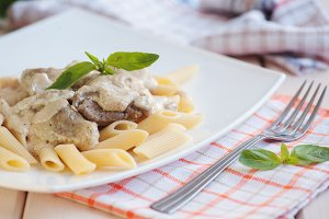 Penne pasta with meat and white sauce on a plate