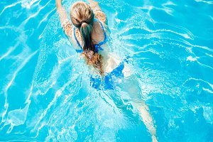 Top view image of young girl swimming in pool