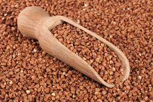 Buckwheat in a wooden scoop as background