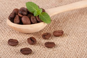 Coffee beans in a wooden scoop with green leaf on sackcloth