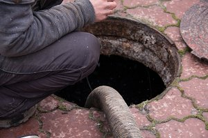 man pumping sewage from the drain hole