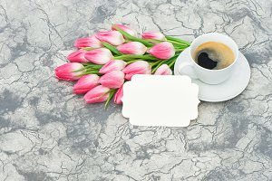 Cup of coffee with tulip flowers
