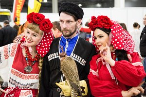 Two ladies and a man in national Russian clothes and a falcon bird