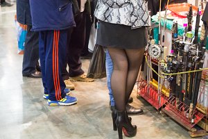 Legs girl in a mini skirt and shoes back, among fishing tackle