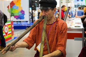 A man in a cap plays simultaneously on two pipes