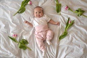 beautiful little baby lying near tulips