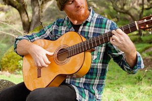 Red haired man playing a guitar