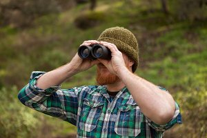 Red haired man looking by binoculars
