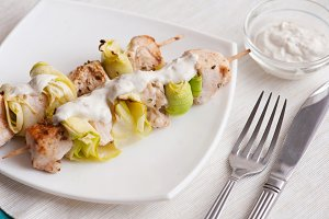 Grilled chicken and zucchini with white sauce on wooden skewers